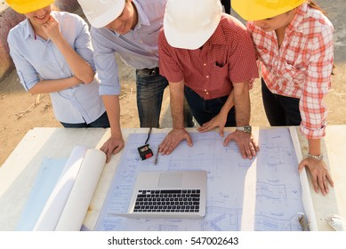 Multi-ethnic group of engineers meeting at construction site in eveing time