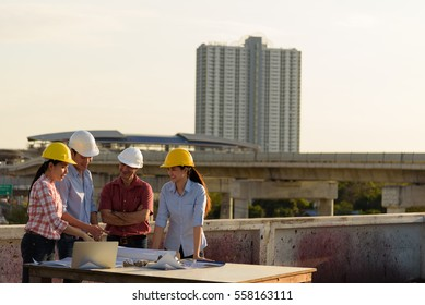 Multi-ethnic group of engineers meeting at terrace on top of construction site in evening time