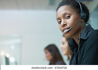 multiethnic group of female customer service representatives talking on the phone, with african woman looking at camera. Horizontal shape, side view, copy space