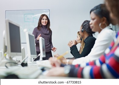 multiethnic group of female customer service representatives in a meeting, adult businesswoman talking. Horizontal shape, side view
