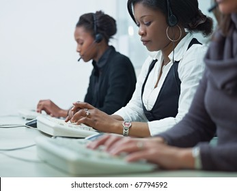 multiethnic group of female customer service representatives talking on the phone and typing on computer keyboard. Horizontal shape, side view, copy space