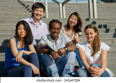 Multiethnic group of five university students sitting on steps of university smiling, metaphor for diversity and international friendship
