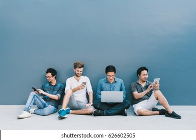 Multiethnic group of four men using smartphone, laptop computer, digital tablet together with copy space on blue wall. Lifestyle with information technology gadget education or social network concept.