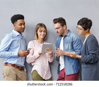 Multiethnic group of four young creative businespeople in stylish clothes holding electronic gadgets, having live discussion, sharing ideas and talking about business strategy and plans in studio