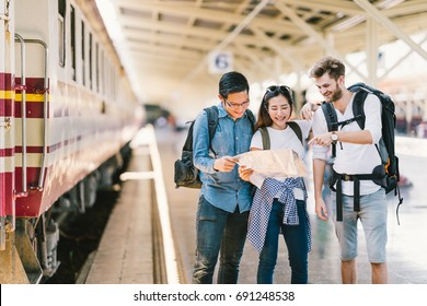 Multiethnic group of friends, backpack travelers, or college students using local map navigation together at train station platform. Asia travel destination, tourism activity, or railroad trip concept