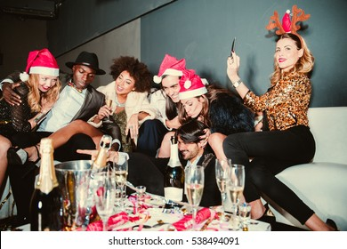 Multi-ethnic group of friends celebrating the end of the year in a nightclub - Sylvester party, clubbers having party on new year's eve