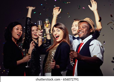 Multi-ethnic group of friends clinking champagne flutes together and wishing happy New Year while having fun in night club, colorful confetti falling