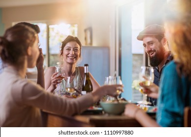 Multi-ethnic group of friends having fun while sharing a meal in a warm and welcoming house. They discuss , while the sun comes in through the window