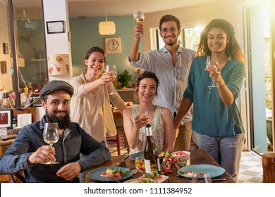 Multi-ethnic group of friends having fun while sharing a meal in a warm and welcoming house. They toast to the camera , while the sun comes in through the window