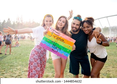 Multiethnic group of friends holding banner Free Hugs at summer music festival