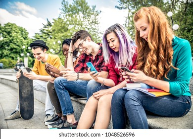Multiethnic group of friends looking down at phone and tablet - concepts about technology addiction and youth