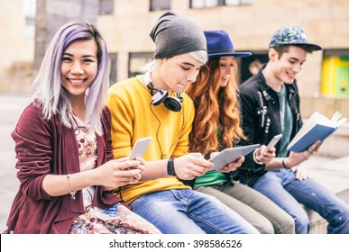 Multiethnic group of friends looking down at phone and tablet, concepts about technology addiction and youth