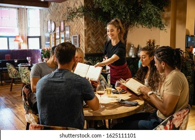 A multi-ethnic group of friends looking at menus together in a restaurant, which have been given to them by a waitress.