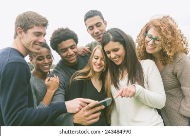 Multiethnic Group of Friends Looking at Mobile Phone