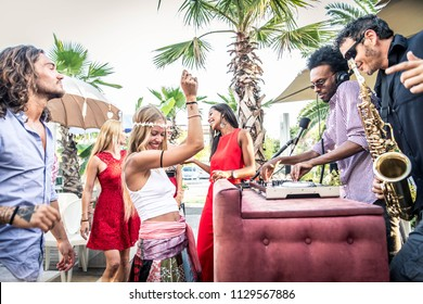 Multiethnic group of friends making party in a lounge bar - Cheerful young adults having fun and celebrating outdoors