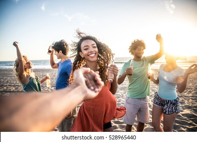 Multi-ethnic group of friends partying on the beach at sunset, pov prospective - Woman taking his boyfriend to dance