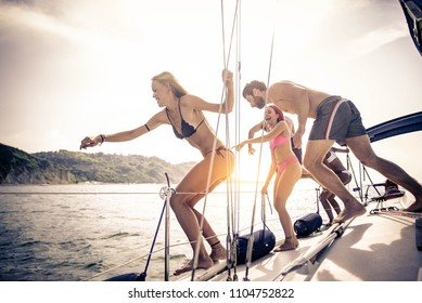 Multiethnic group of friends sailing on a boat - Summer holidays, young adults having fun