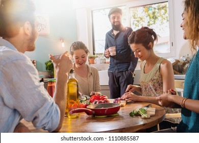 Multi-ethnic group of friends sharing a good time while preparing lunch in the kitchen. Everyone's having fun while the morning sun comes in through the window