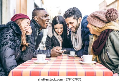 Multi-ethnic group of friends sitting in a bar and drinking coffee and watching a funny video on a cellular phone - Cheerful students meeting in a coffee house for a break