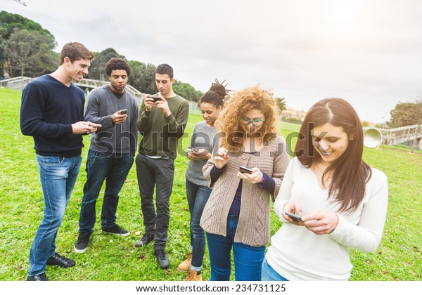 Multiethnic Group of Friends, Smart Phone Addicted. Everyone is looking at his own Phone without caring of other persons around him.