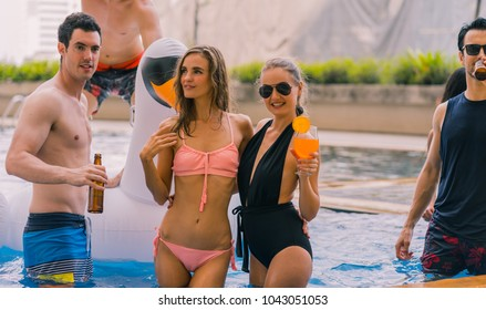 Multi-ethnic group of friends in a swimming pool - Young happy people having fun and enjoying summertime in pool party