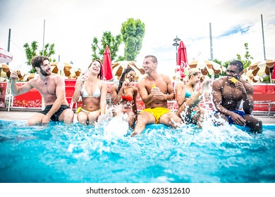 Multi-ethnic group of friends in a swimming pool - Young happy people having fun and enjoying summertime in a aquapark