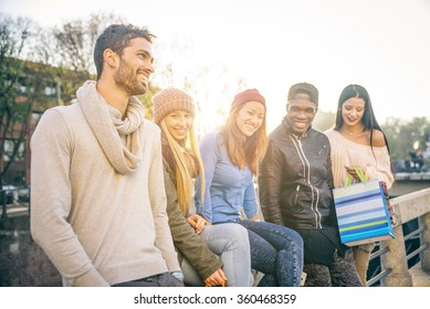 Multi-ethnic group of friends talking and laughing outdoors - Happy students having fun while having a conversation outdoors