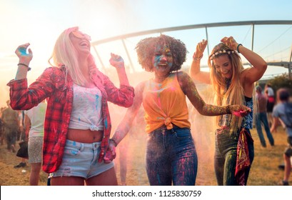 Multiethnic group of friends throwing colorful powder at holi festival