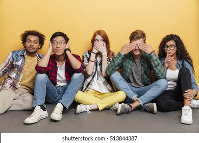 Multiethnic group of funny young friends covered eyes, ears and mouth over yellow background