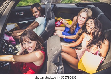 Multiethnic group of girls driving a convertible car - Four beautiful women having fun while buying some presents in a mall in Beverly Hills