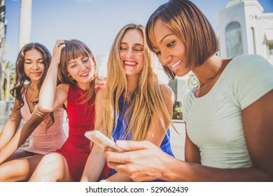 Multiethnic group of girls shopping - Four beautiful woman having fun while looking at smartphone