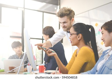 Multiethnic group of happy business people working together and brainstorming in office. Use computer, laptop, tablet, mobile phone.