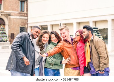 Multiethnic group of happy friends having fun taking selfie during winter school break outdoors -  Different culture young students cheerful moment together using modern technology at old town center