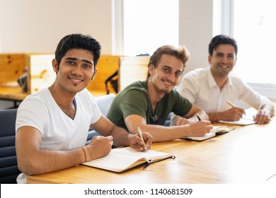 Multiethnic group of happy students posing in classroom. Three Indian and Caucasian trainees writing in notebooks and smiling at camera. Corporate education concept