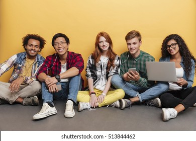 Multiethnic group of happy young friends listening to music from smartphone and using laptop over yellow background