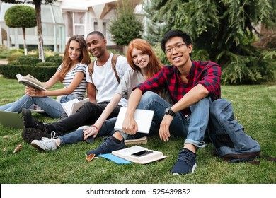 Multiethnic group of happy young people reading books on lawn outdoors