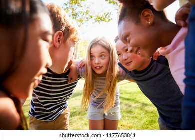 Multi-ethnic group of kids embracing, looking at each other
