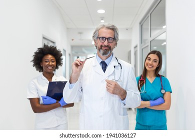 A multi-ethnic group of medical staff . They are dressed in medical scrubs and white lab coats with stethoscopes around their necks. Some standing in the back. The focus is on an mature man in front