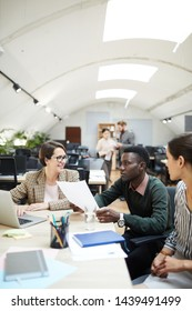 Multi-ethnic group of people discussing work while collaborating in office, copy space