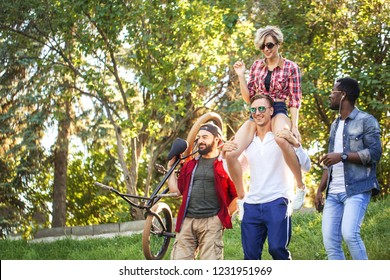 Multi-ethnic group of people going with their male friend to bmx contest in the urban summer park, Young cheerful man giving piggyback ride to his blonde girlfriend. Fun and Bonding Concept.