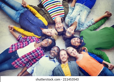 Multiethnic Group of People Holding Hands and Lying Down