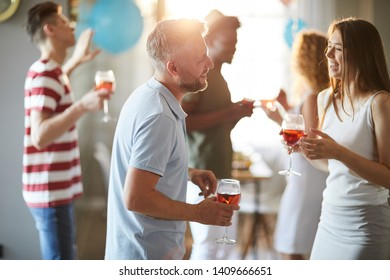 Multi-ethnic group of people mingling and chatting while enjoying fancy house party, copy space