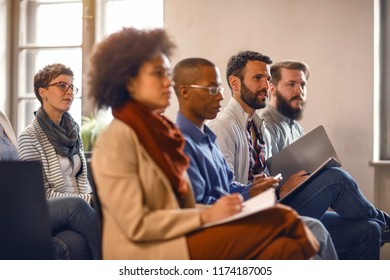 Multiethnic group of people in public on meeting listens lecturer