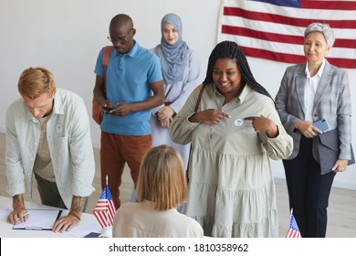 Multi-ethnic group of people registering at polling station decorated with American flags on election day, focus on smiling African woman pointing at I VOTE sticker, copy space