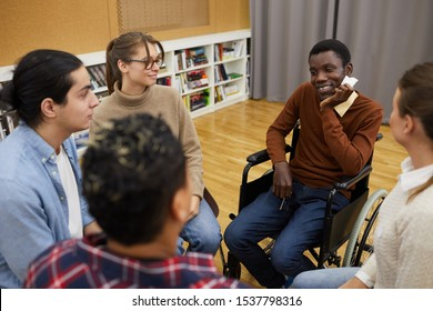 Multi-ethnic group of people sitting in circle, focus on handicapped African man sitting in wheelchair during support meeting, copy space
