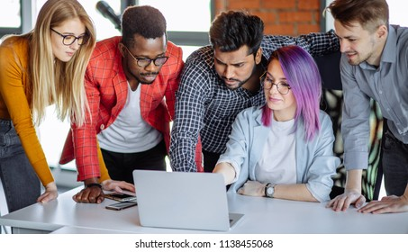 Multi-Ethnic Group of People standing near woman with violet hair, sharing with her laptop, reading all together amazing news.