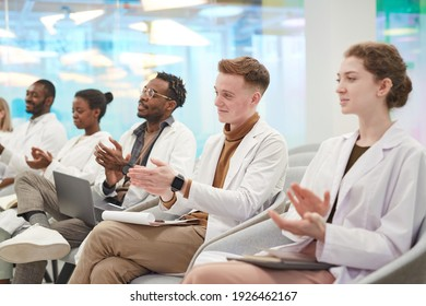 Multi-ethnic group of people wearing lab coats sitting in row in audience and applauding at medical seminar, copy space