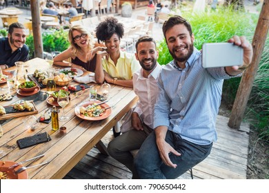 Multiethnic group of pretty women and handsome men friends taking selfie at restaurant and looking happy.