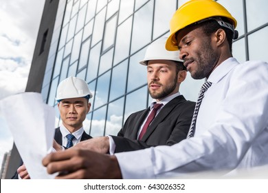 Multiethnic group of professional architects in helmets working with blueprint outside modern building