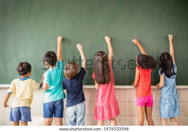 Multi-ethnic group of school children drawing on the chalkboard